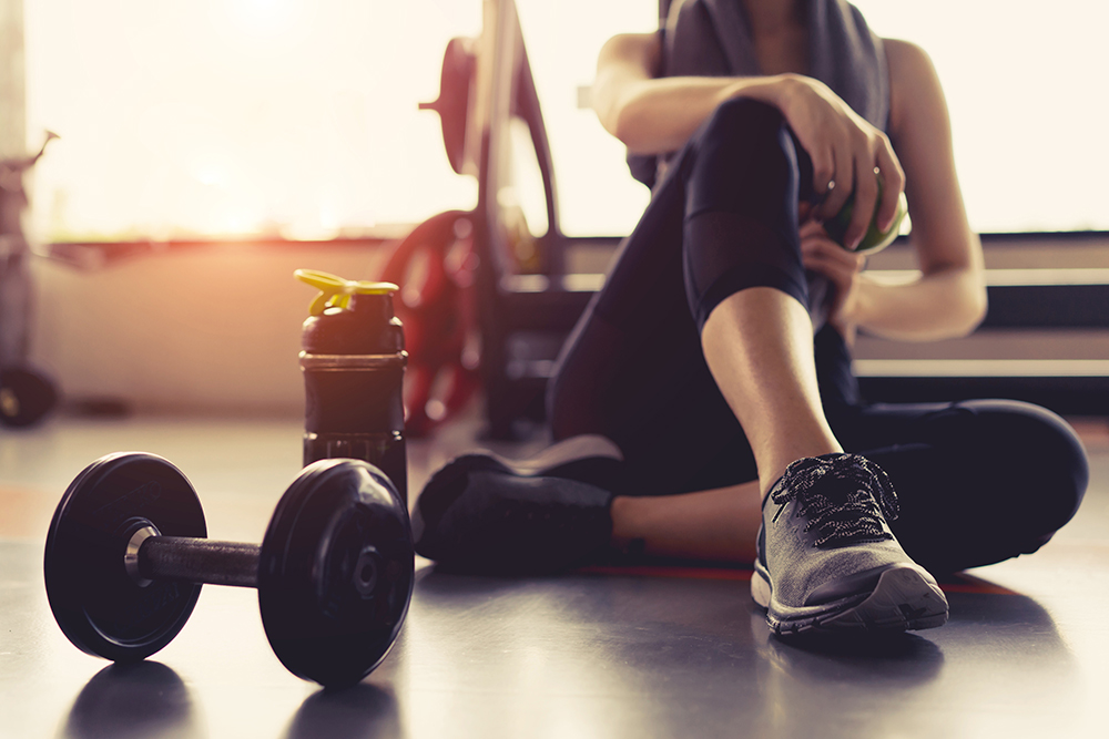 Woman exercise workout in gym fitness breaking relax holding apple fruit after training sport with dumbbell and protein shake bottle healthy lifestyle bodybuilding.